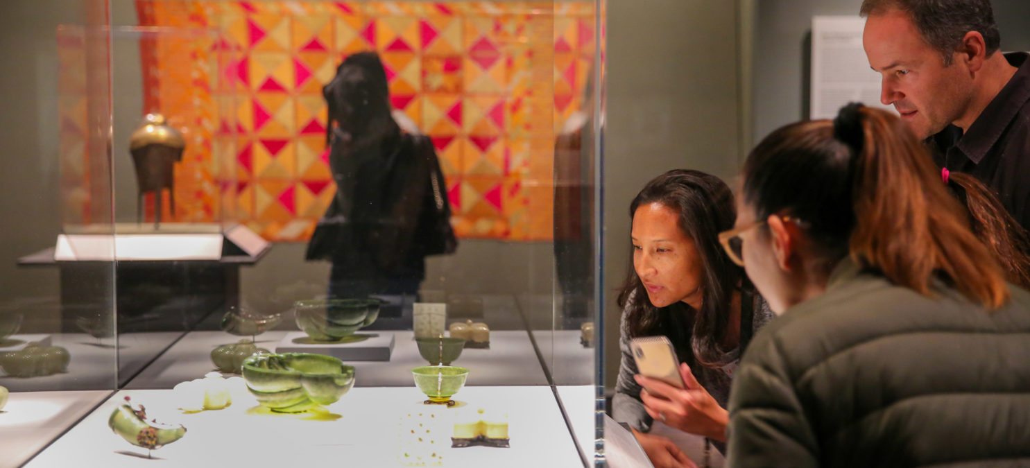 Three museum visitors look at small green objects in a glass case.