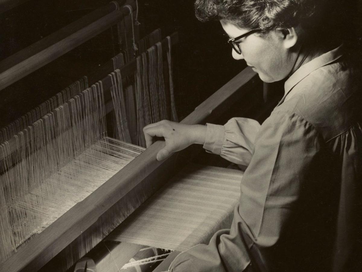 A woman sitting at a loom.